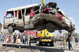 A damaged bus which was hit by a remote control bomb is lifted by a crane on the outskirts of Kabul, Afghanistan, August 7, 2012.