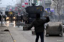 A protester throws a stone at police during clashes in Pristina, Kosovo January 9, 2016. Demonstrators in Kosovo fought running battles with police and briefly set fire to government headquarters on Saturday in the latest violence in the young Balkan