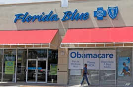 FILE - A person walks by a health care insurance office in Hialeah, Florida. National polls in the U.S. have shown voters favored keeping Obamacare, not Republican plans to repeal it.
