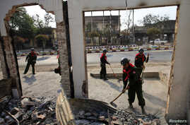 Soldiers work to clean debris in Meikhtila, March 24, 2013, following clashes between Buddhists and Muslims in the city.
