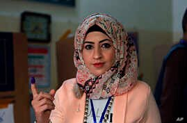 An Iraqi woman shows her ink-stained finger after casting her vote in the country's parliamentary elections in Baghdad, May 12, 2018. Polls opened across Iraq on Saturday in the first national election since the declaration of victory over the Islami