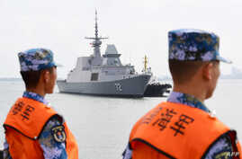 This photo taken on October 21, 2018 shows Chinese sailors watching as a Singapore navy ship arrives at a military port in Zhanjiang, in China's southern Guangdong province.