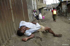 """A man sleeps on the streets after drinking distilled traditional alcoholic liquor, locally known as """"chang'aa"""", in the suburbs of Nairobi May 9, 2014"""