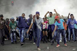 Protesters sing and chant in front of a burning barricade in the Ennerdale, Johannesburg township, South Africa, May 9, 2017.