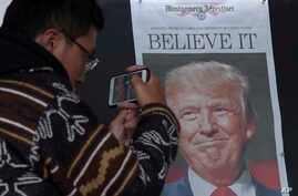 Zheng Gao of Shanghi, China, photographs the front pages of newspapers on display outside the Newseum in Washington, Nov., 9, 2016, the day after Donald Trump won the presidency.