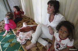 UNHCR's Representative in Lebanon Ninette Kelley sits with Syrian refugee children inside a makeshift room during her visit to the refugees on the occasion of the World Refugee Day, in Alman town, in the Shouf area in Mount Lebanon, Lebanon, June 20,