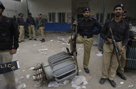 Pakistani police officers stand guard at the office of local electrical company attacked by angry protesters to condemn  electricity shortages in Lahore, Pakistan, March 27, 2012. Pakistan is suffering from a serious energy crisis leading to closure