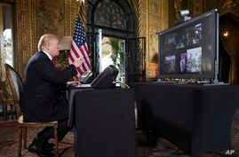 President Donald Trump points to the video screen during a Christmas Eve video teleconference with members of the mIlitary at his Mar-a-Lago estate in Palm Beach, Fla., Dec. 24, 2017.