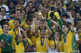 Brazil's Neymar (C) hoists the trophy as he celebrates on the podium with his teammates after winning their Confederations Cup final soccer match against Spain at the Estadio Maracana in Rio de Janeiro Jun. 30, 2013.