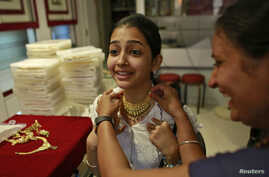 A girl tries a gold necklace inside a jewellery showroom in Mumbai, Apr. 16, 2013.