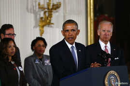 U.S. President Barack Obama stands with Vice President Joe Biden (R) and family members of shooting victims while delivering a statement on steps the administration is taking to reduce gun violence in the East Room of the White House in Washington, J
