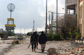 Rebel fighters walk around al-Hamidiyeh base, one of two military posts they took control of from forces loyal to Syria's President Bashar al-Assad in the northwestern province of Idlib, Dec. 15, 2014.
