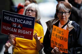 Jo Ann Waker-Ferrand, left, and Jan Miller, both of Denver, wave their placards during a protest, June 23, 2017, in downtown Denver, against the Republican health bill that was recently unveiled in the U.S. Senate.