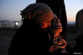 FILE - A Syrian refugee holds her baby next to a bonfire as she waits to cross the Greek-Macedonian border, near the village of Idomeni, Greece, Jan. 21, 2016.