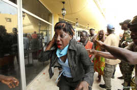 An injured supporter of Ivory Coast's Laurent Gbagbo reacts outside the premises of Hotel Golf, where Gbagbo was being held after his arrest, in Abidjan, April 11, 2011.