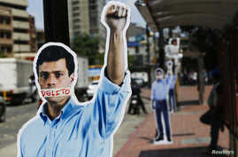 Cardboard figures of jailed opposition leader Leopoldo Lopez with his mouth covered with the word 'Crime' are seen during a gathering in support of him in Caracas June 4, 2014. The oppposition leader Lopez is attending the third day of a hearing.