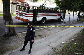 A policeman secures a crime scene after a bus driver was killed by suspected gang members during a suspension of public transport services in San Salvador, July 27, 2015.