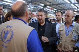 German Economy Minister Sigmar Gabriel, center, visits a supermarket at the Zaatari refugee camp near Mafraq, north of Amman, Jordan, Sept. 22, 2015.