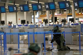 A bomb disposal expert checks a luggage near the site of a blast at a terminal in Shanghai's Pudong International Airport, China, June 12, 2016.