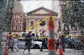 New Yorkers pass a shattered storefront window on W. 23rd St. in Manhattan. The window was hit by shrapnel from the bomb that exploded across the street Saturday evening