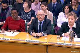 Oxfam's chief executive Mark Goldring, center, Oxfam's international director Winnie Byanyima (left) and Oxfam's chair Caroline Thomson attend a hearing of the British parliament's International Development Committee in London, Britain, Feb. 20, 2018