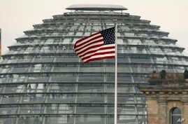 FILE - The U.S.  flag flies  on top of the U.S. embassy in front  of the  Reichstag building  that houses the German  Parliament, Bundestag, in Berlin, Germany.