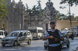 A Turkish police officer secures the road that leads to Istanbul's Dolmabahce Palace, background, Aug. 19, 2015, following an armed attack.