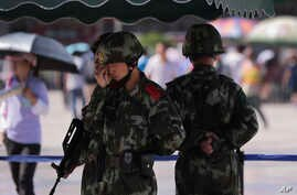 FILE - Chinese paramilitary police stand watch at a Beijing railway station, guarding against attacks by Uighur militants, Sept. 3, 2014.