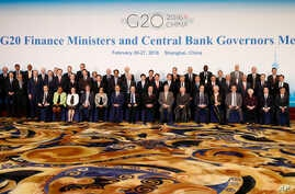 Officials led by host country officials Chinese Finance Minister Lou Jiwei, center left in front, and People's Bank of China Governor Zhou Xiaochuan, center right in front, pose for a family photo of G20 Finance Ministers and Central Bank Governors M