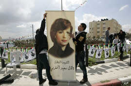 FILE - Palestinians inaugurate a square to commemorate Dalal Mughrabi, a Palestinian female militant who killed dozens of civilians in a 1978 bus hijacking in Israel, seen in a portrait, in the West Bank city of Ramallah, March 13, 2011.