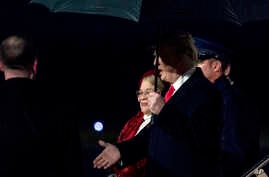 President Donald Trump accompanied by Dr. Alveda King, niece of civil rights activist Dr. Martin Luther King Jr., center, arrives at Dobbins Air Reserve Base in Marietta, Georiga, Jan. 8, 2018,