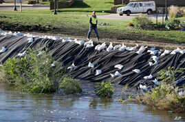 A worker walks across a levee overlooking the flood swollen Cedar River, Tuesday, Sept. 27, 2016, in Cedar Rapids, Iowa.  An elaborate system of temporary floodwalls largely protected Cedar Rapids homes and businesses as the river reached its second-
