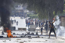 Supporters of Islamist group Ansar al-Sharia clash with riot police at Hai al-Tadamon in Tunis May 19, 2013.