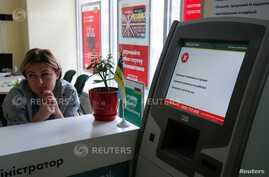 An employee sits next to a payment terminal out of order at a branch of Ukraine's state-owned bank Oschadbank after Ukrainian institutions were hit by a wave of cyber attacks earlier in the day, in Kiev, Ukraine, June 27, 2017.  REUTERS/Valentyn Ogir