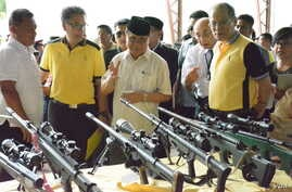 Moro Islamic Liberation Front Chairman Al Haj Murad Ebrahim (C) shows Philippine President Benigno Aquino (R) the weapons that Front rebels turned in as part of the decommissioning process of a peace pact between the Philippines and the rebels, in Su