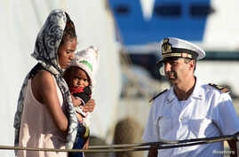 A woman holds a child after disembarking from the Italian Navy ship Borsini in the Sicilian harbour of Palermo, southern Italy, July 20, 2016.