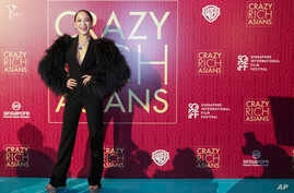 """Actress Fiona Xie poses for photographers as she arrives for the red carpet screening of the movie """"Crazy Rich Asians,"""" Aug. 21, 2018, in Singapore."""