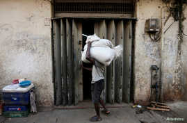 FILE - A laborer tries to open a door at a store room as he carries sacks of rice near a main market in Colombo, Sri Lanka, Feb. 21, 2017.