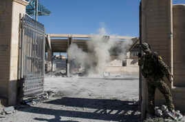 A member of the U.S.-backed Syrian Democratic Forces SDF throws a bomb to check for more explosives as they clear the syadium that was the site of Islamic State fighters' last stand in the city of Raqqa, Syria, Oct. 18, 2017.