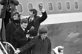 This Feb. 7, 1964 file photo shows The Beatles, from left, Ringo Starr, John Lennon, Paul McCartney and George Harrison arriving in New York at John F. Kennedy airport