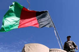 An Afghan National Directorate of Security (NDS) police stands guard next to an Afghanistan flag at a guard post of a police camp in Now Zad district in Helmand province, Afghanistan. (File)