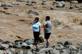 A couple looks at the overflowing Maipo River in San Alfonso, Santiago, Chile, Feb. 26, 2017.