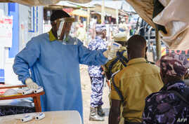 A medical assistant checks the temperature of people from Democratic Republic of Congo (DRC) at the Ebola screening point bordering with DRC in Mpondwe, western Uganda, on Dec. 12, 2018.