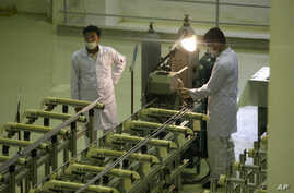 FILE - Iranian technicians work at a facility producing uranium fuel outside of Isfahan, 410 kilometers south of the capital, Tehran.