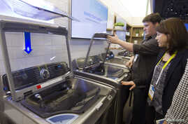 A couple examines a Samsung washing machine at the International Consumer Electronics Show (CES) in Las Vegas, Nevada, Jan. 6, 2015.