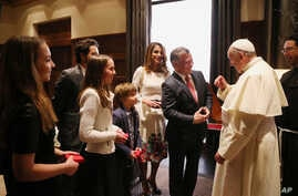 Jordan's King Abdullah II, center right, with his wife Queen Rania, standing behind him, talks with Pope Francis as their four children listen at the royal palace in Amman, May 24, 2014.
