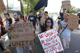 Demonstrators march in a Labor Day parade, Monday, Sept. 3, 2012, in Charlotte, North Carolina.