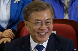 Moon Jae-in of the Democratic Party smiles as and leaders and members of the party watch local broadcast media's results of exit polls in the presidential election in Seoul, South Korea, May 9, 2017.