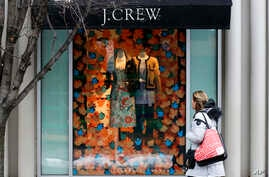 FILE - a shopper passes a display in the window of a J. Crew store in the Shadyside shopping district of Pittsburgh.