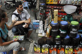 FILE - Tourists try coffee before making purchases at a shop in Hanoi, Aug. 20, 2013.